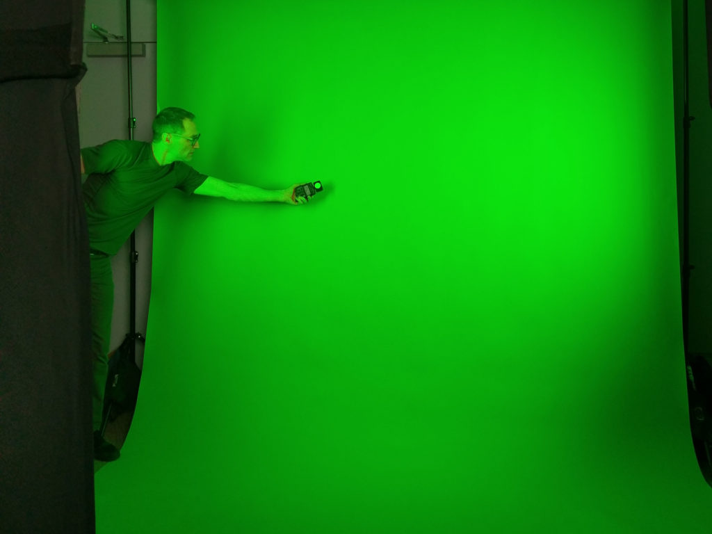 Nick checking exposure across a paper green screen backdrop for a talking head piece.